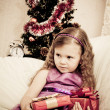 Little girl at a Christmas fir-tree. — Stock fotografie