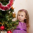 Foto de Stock  : Little girl at a Christmas fir-tree.
