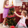 图库照片: Little girls at a Christmas fir-tree.