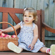 Little girl sits on a bench with a basket of apples — Stock Photo #7629626