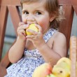 Little girl with appetite is a juicy pear — Stock Photo