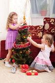 Little girls at a Christmas fir-tree. — Stock Photo