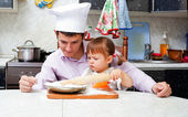 Father with a small daughter do dough for pies — Stock Photo
