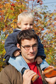 Small son sits on shoulders at the father — Stock Photo