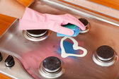 Hand of the person in a rubber glove cleans a kitchen gas cooker — Stockfoto