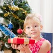 Little girl at a Christmas fir-tree — Stock Photo