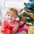 Stock Photo: Little girl at a Christmas fir-tree