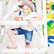 Girl in a white T-shirt and a cap bedaubed with bright paints — Stockfoto