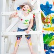 Stock Photo: Girl in a white T-shirt and a cap bedaubed with bright paints