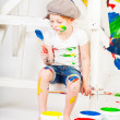 Foto Stock: Girl in a white T-shirt and a cap bedaubed with bright paints