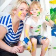 Girl in a white T-shirt with mum, bedaubed with bright paints — Stock Photo
