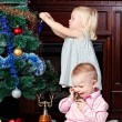 Happy children at a Christmas fur-tree — Stok fotoğraf