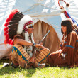 Stock Photo: Group of North AmericIndians about wigwam