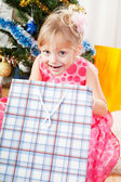 Little girl at a Christmas fir-tree — Stockfoto