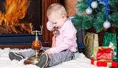 Niño en una habitación con chimenea se sienta en un árbol de navidad la piel — Foto de Stock
