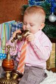 Niño se sienta en un árbol de navidad la piel y llama por teléfono — Foto de Stock