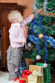 Little boy dresses up a Christmas fur-tree — Stock Photo