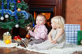 Niños felices en un árbol de navidad la piel — Foto de Stock