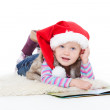Little blonde girl in a fur jacket and a red Santa's cap lying on the floor — Stock Photo #7947609