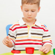 Stock Photo: Little boy paints paints sitting at the table