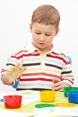 Little boy paints paints sitting at the table — Foto Stock
