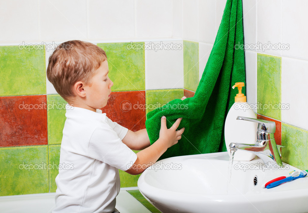 Boy in a bathroom wipes the washed up hands a towel  Stock Photo #7947620