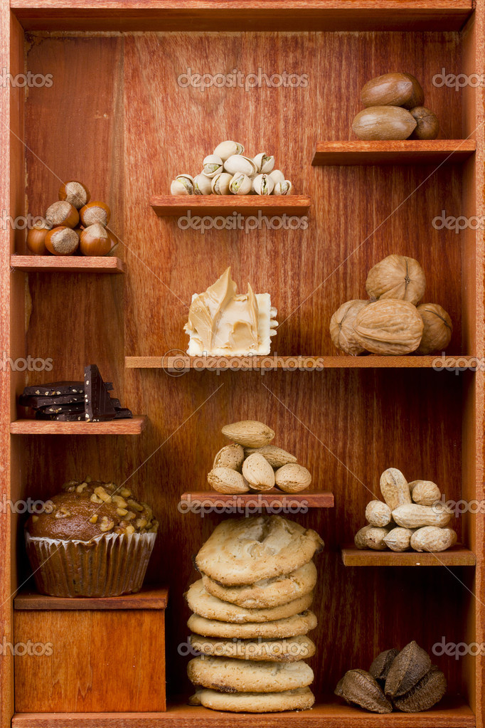 Assortment of different nuts and foods with nuts in them in a wooden shelf. — Stock Photo #6851435