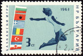 Jumping athlete on post stamp — Stock Photo