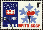 Olympic torch and emblem on post stamp — Stock Photo