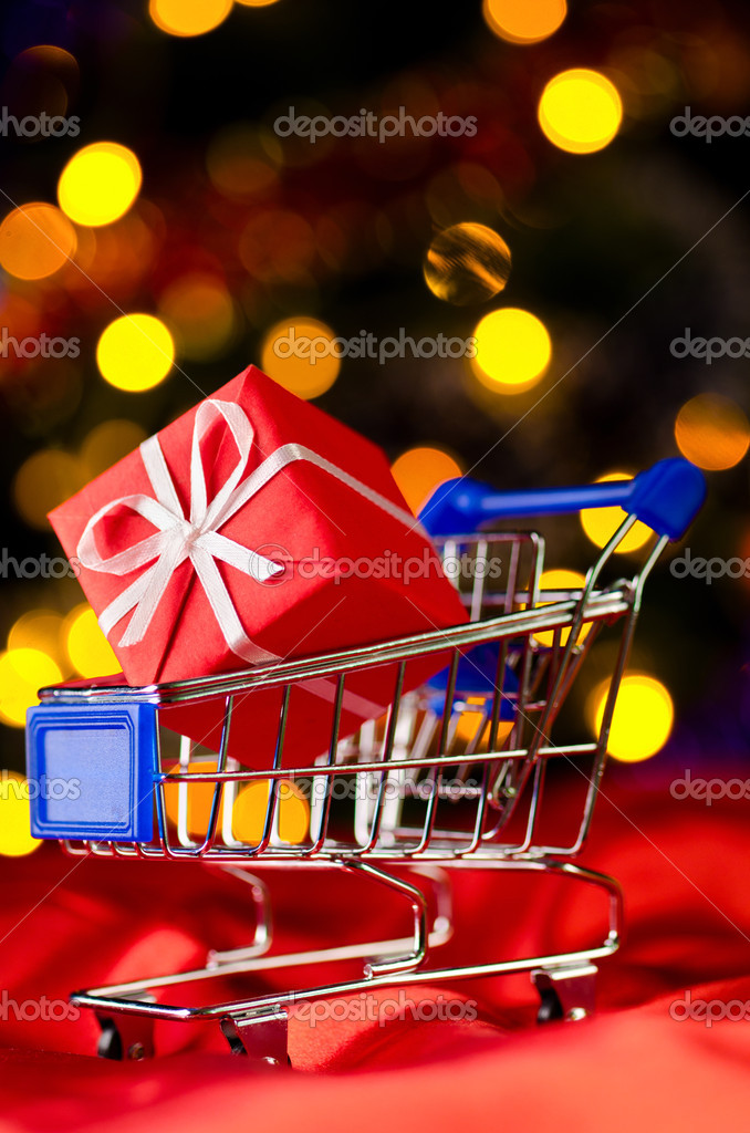 Shopping cart with decorative gift box against blurred lights on christmas tree — Stock Photo #7253697