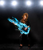 Woman is playing rock music on fiery guitar — Stock Photo