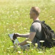 Guy with computer on green field — Stock Photo #7161404