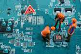 Miniature engineers fixing error on chip of motherboard — Stock Photo
