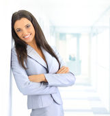 Portrait of beautiful businesswoman leaning against white wall in office — Stock Photo