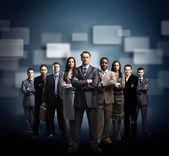 ビジネス チームは、暗い背景の上に立っている若いビジネスマンの形成 — ストック写真