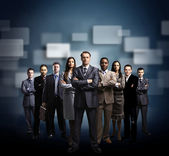 Business team formed of young businessmen standing over a dark background — Stok fotoğraf