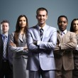 Business team formed of young businessmen standing over a dark background — Stock Photo