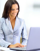 Young businesswoman working on laptop computer at office, smiling — Stock Photo