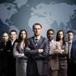 Businessmen standing in front of an earth map — Stock Photo #7500644