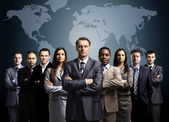 Businessmen standing in front of an earth map — Stockfoto