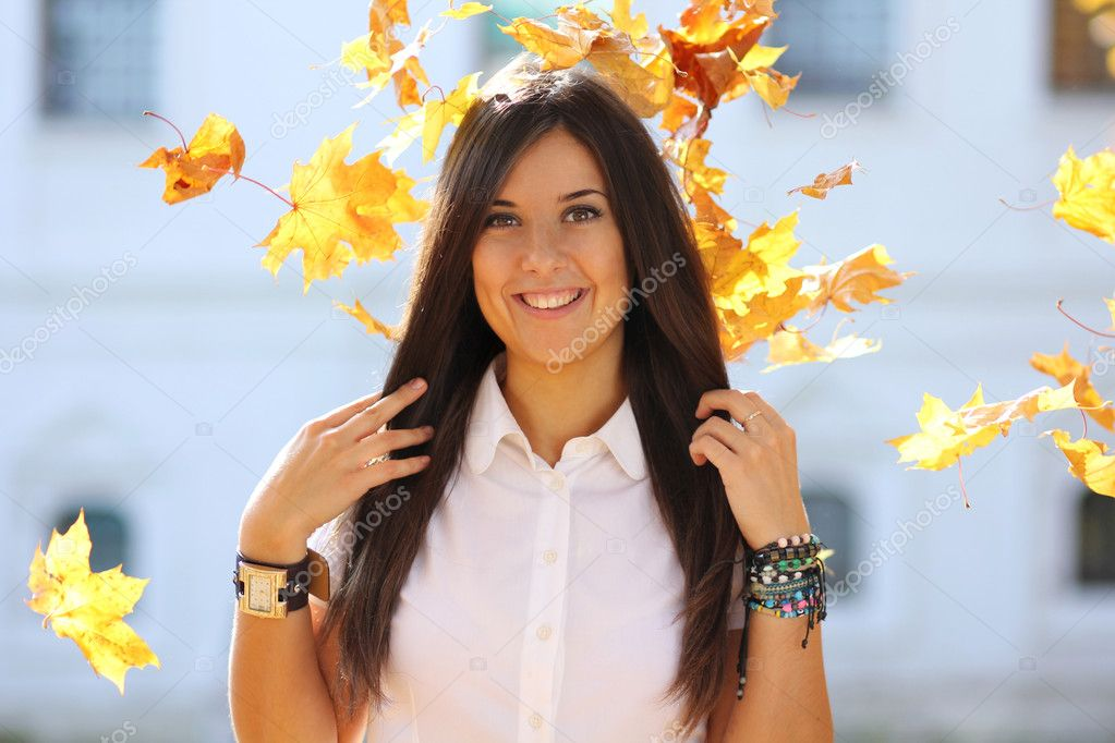 Portrait of a happy woman against yellow leaves — Stock Photo #7154200