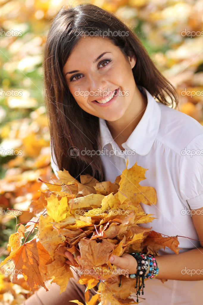 Young beautiful girl with a bouquet of maple leaves — Stock Photo #7154215