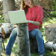 Stock Photo: Blond woman having fun with laptop outdoors