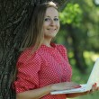 Blond woman having fun with laptop outdoors — Stock Photo