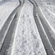Close up tyre tracks in snow on a road. - Stock Photo