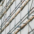 Close up building covered by scaffolding and white tarpaulin. - Stock Photo