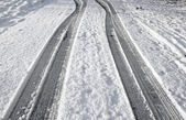 Close up tyre tracks in snow on a road. — Stok fotoğraf