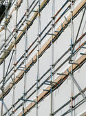 Close up building covered by scaffolding and white tarpaulin. — Foto de Stock