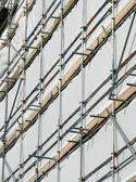 Närbild av byggnaden omfattas av byggnadsställningar och vit presenning. — Stockfoto