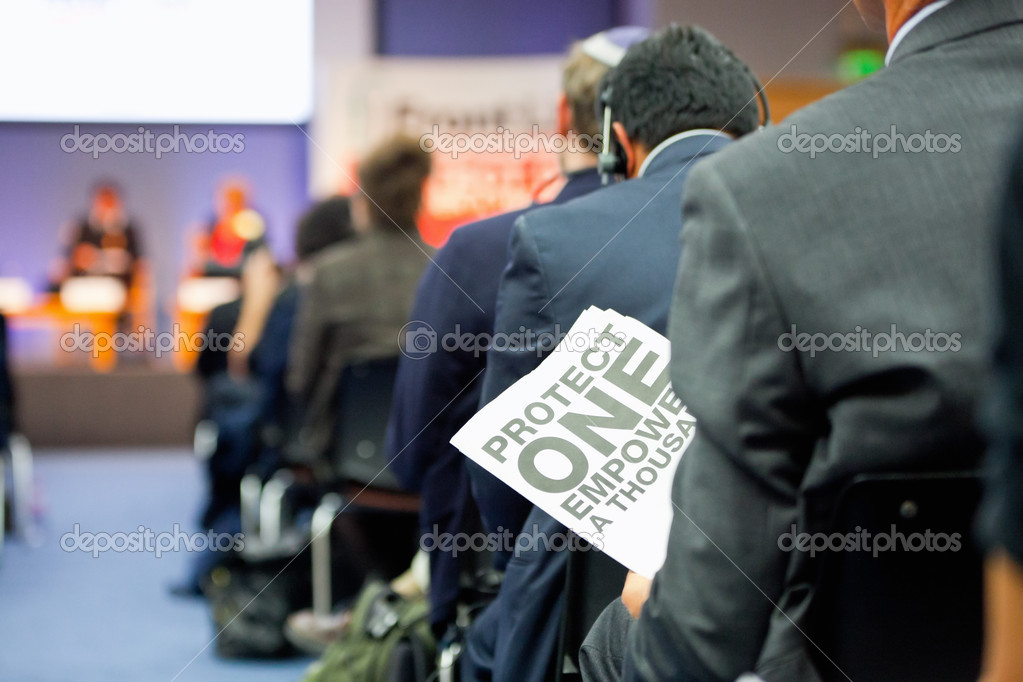 Man  holding a poster with sign 'Protect One Empower a Thousands' during presentation in buisy  auditorium — Stock Photo #6876713